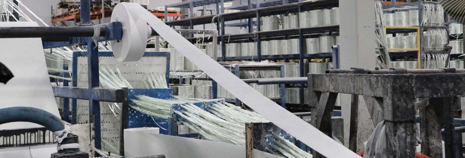 glass fibers being pulled through a machine onto a spool into a sheet of cohesive white fiberglass composite
